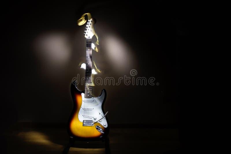 Menez la guitare électrique de rayon de soleil, allumant la peinture avec la lumière images libres de droits