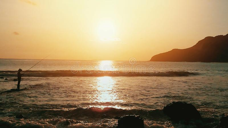 Menganti strandsolnedgång arkivbild