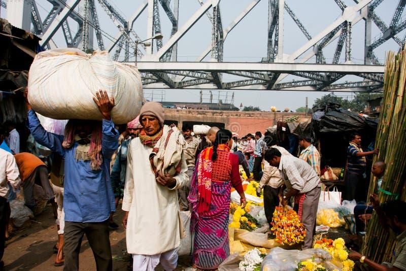 Menge von asiatischen Leuten hetzen durch die Blumenmarktreihen in Kalkutta