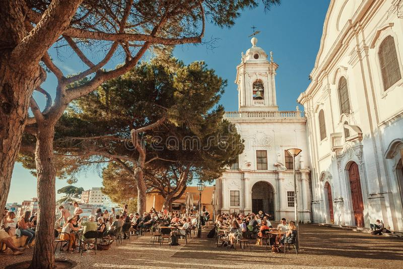 Menge von den Besuchern Restaurants des im Freien trinkend und auf Terrasse mit schöner Stadtansicht entspannend lizenzfreie stockbilder