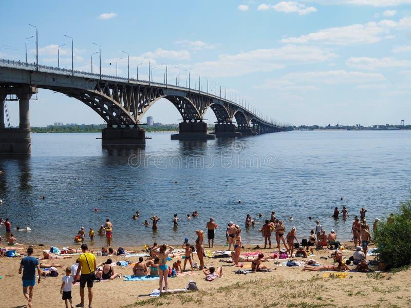 Menge von den Leuten, die auf einem nicht autorisierten Strand nahe der Stadtbrücke über dem Fluss an einem anormalen heißen Tag  lizenzfreies stockbild