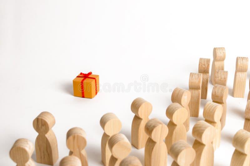 Menge von Leuteblicken auf die Geschenkbox Das Konzept des Findens des perfekten und besten Geschenks Das Angebot und das Geben v lizenzfreie stockfotografie