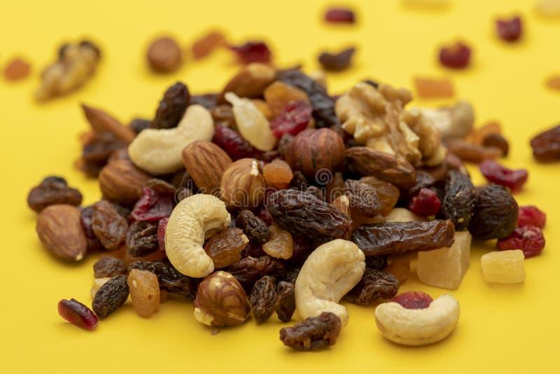 Mengeling van droge vruchten en noten op een gele achtergrond stock afbeeldingen