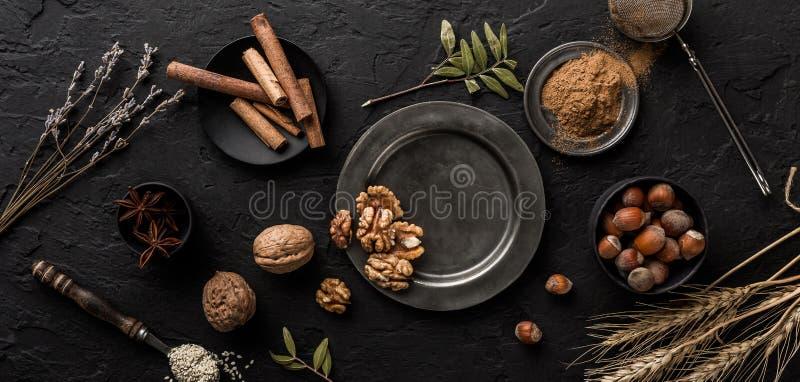 Mengeling van noten en kruiden voor bakselcakes in kom en lepel, kaneel, steranijsplant, hazelnoten, okkernoten, tarwe, lavendel  stock afbeelding