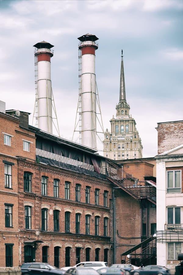Mengeling van twee pijpen en gebouwen van verschillende tijden tegen blauwe hemel De oude Industriële bouw van de fabriek van roo stock fotografie