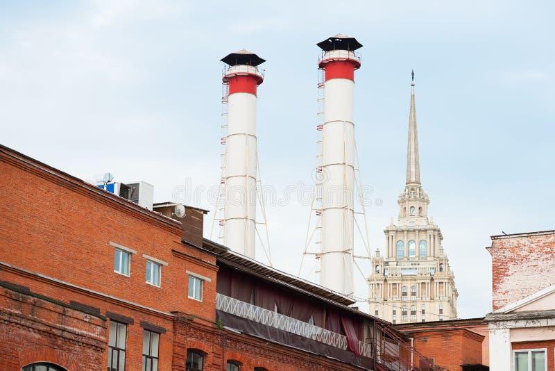 Mengeling van twee pijpen en gebouwen van verschillende tijden tegen blauwe hemel De oude Industriële bouw van de fabriek van roo royalty-vrije stock afbeelding