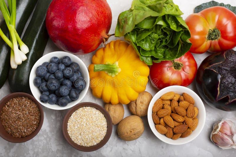 Mengeling van verse gezonde vegetarische ingrediënten van groenten, noten, zaden, zemelen, fruit en bessen op een grijze cementac stock afbeelding