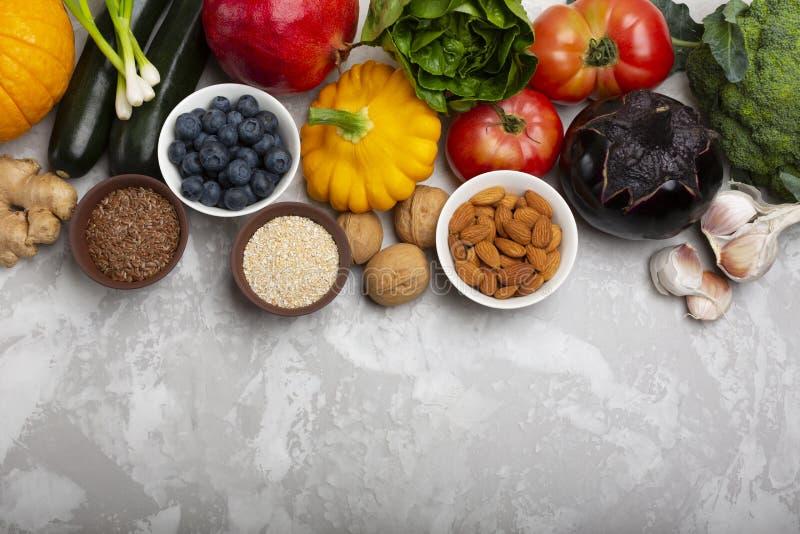 Mengeling van verse gezonde vegetarische ingrediënten van groenten, noten, zaden, zemelen, fruit en bessen op een grijze cementac royalty-vrije stock foto