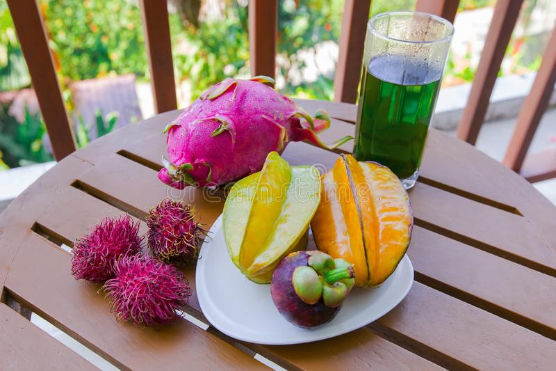 Mengeling van verse vruchten van Thailand, draakfruit, rambutan, carambola, mangostan en glas smaragdgroene thee Gesneden mooie v stock foto's