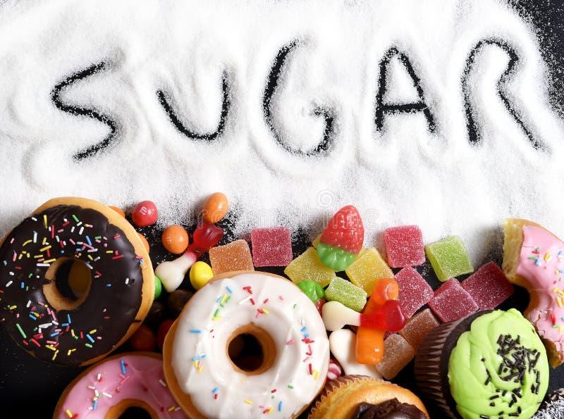Mengeling van zoete cakes, donuts en suikergoed met uitgespreid en geschreven suiker tekst in ongezonde voeding
