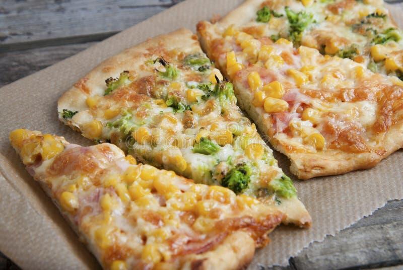 Mengelingsplakken van eigengemaakte pizza met kaas, suikermaïs, bacon en spinaziebladeren, op houten achtergrond royalty-vrije stock fotografie