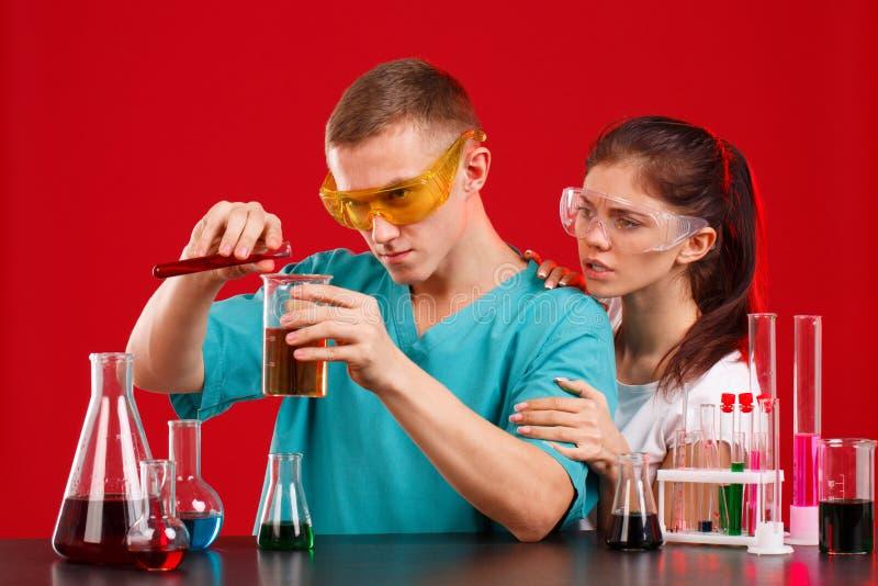 Mengen de het laboratorium hulpmeisje en jongen, verschillende vloeistoffen, toevoegend vloeistof van een kleine bol aan grote  royalty-vrije stock foto