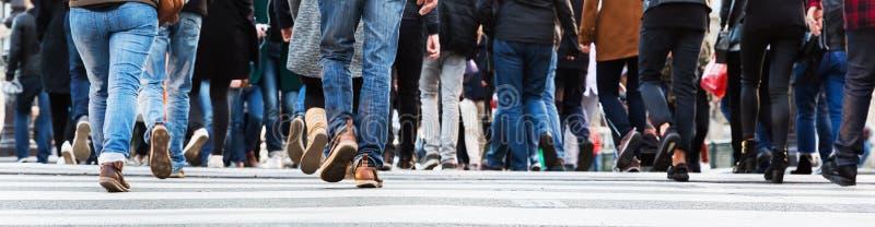 Mengen von Leuten in der Bewegungsunschärfe, die eine Stadtstraße kreuzt stockfotos