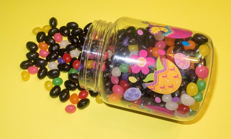 Mengsel van gekleurde geleibonen die voor Pasen-vakantie uit plastic Pasen-suikergoedcontainer morsen royalty-vrije stock afbeeldingen