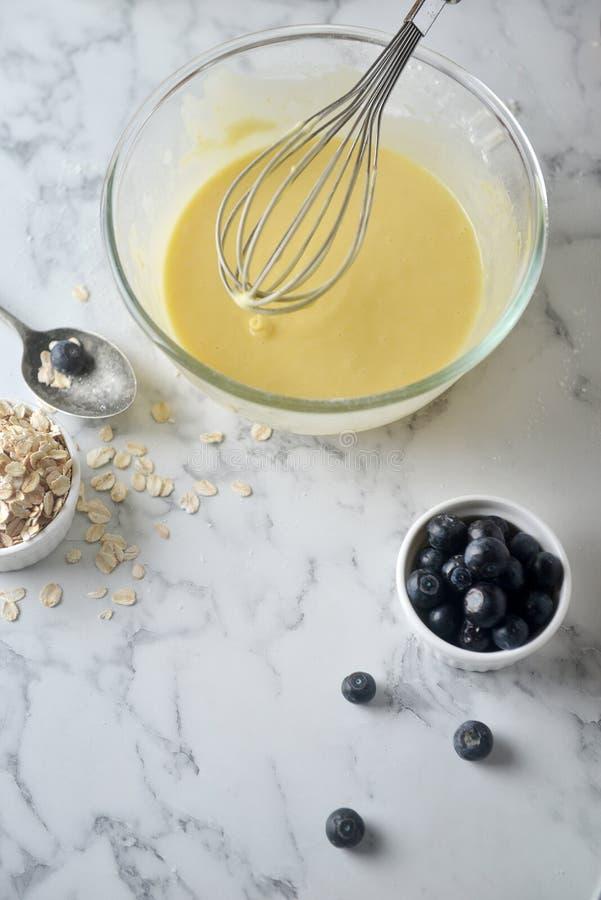 Mengt eieren, bloem en melk in kom met zilveren draad zwaai Concept het Koken van ingrediënten en methode op witte marmeren achte royalty-vrije stock fotografie
