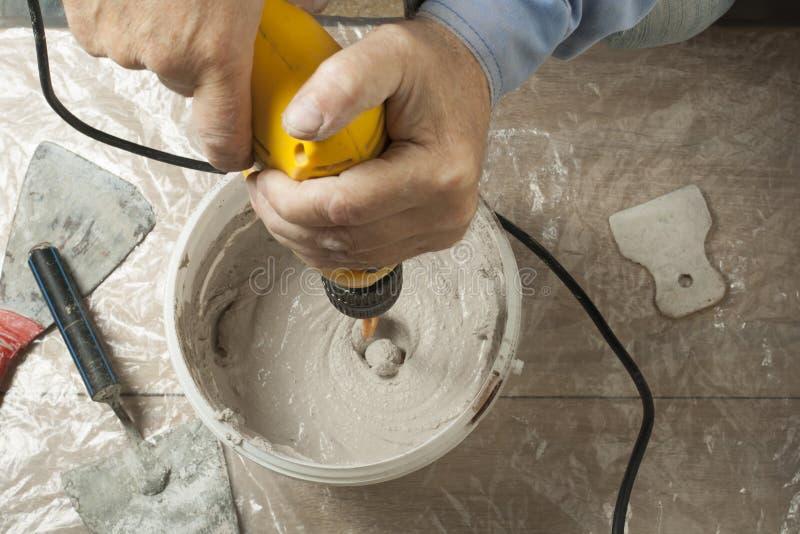 Mengt pleisteroplossing in een emmer, die elektrische boor gebruiken royalty-vrije stock fotografie