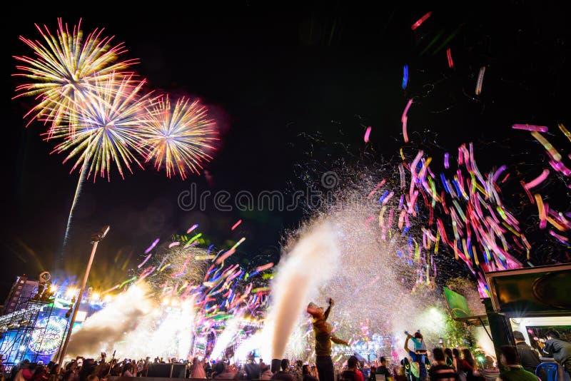 Menigte het letten op ballons, vuurwerk en het vieren van nieuwe jaarvooravond royalty-vrije stock foto's