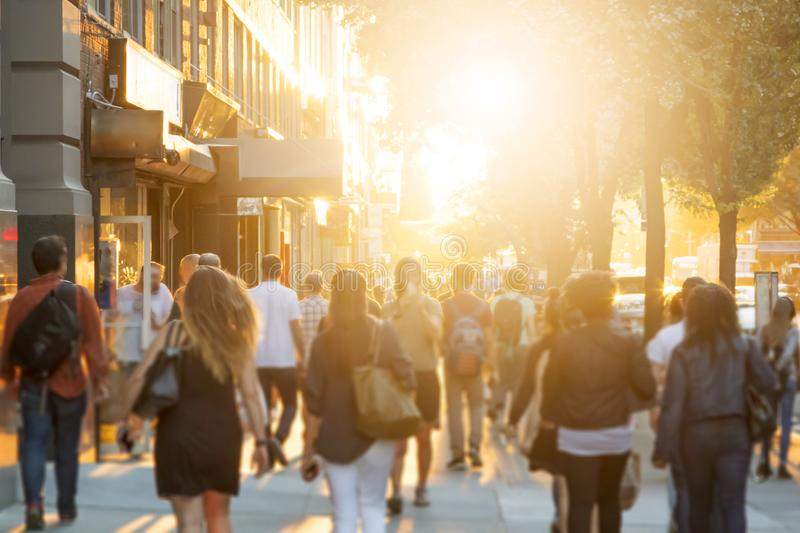 Menigte van anonieme mannen en vrouwen die onderaan een stedelijke stoep lopen stock afbeelding
