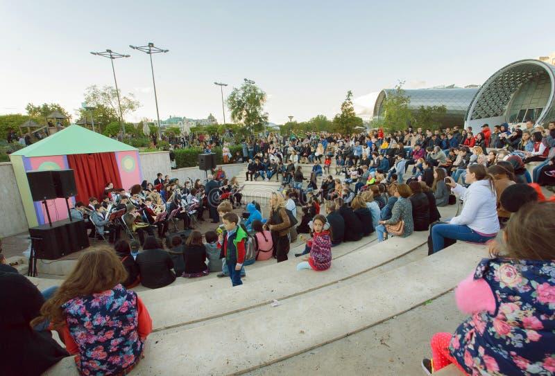 Menigte van jongeren die op een overleg van een orkest bij park Rike tijdens festival in Tbilisi zitten royalty-vrije stock foto