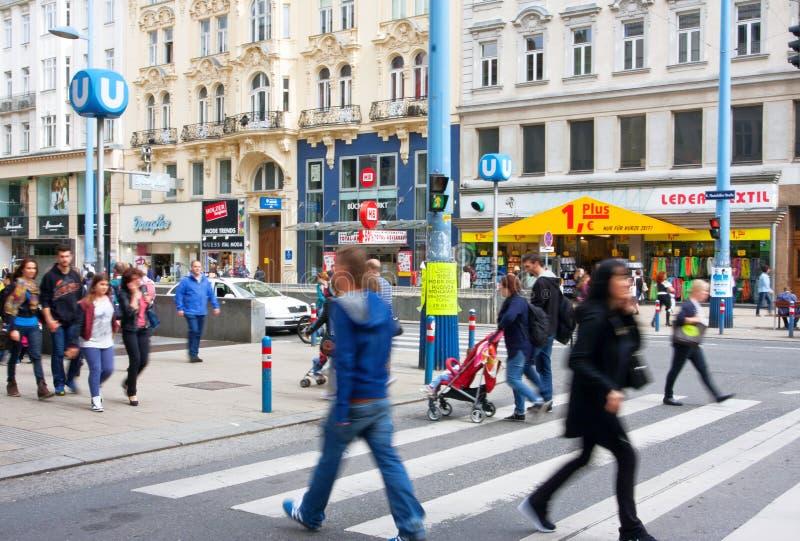 Menigte van mensen die de straat van Oostenrijkse ca kruisen stock foto