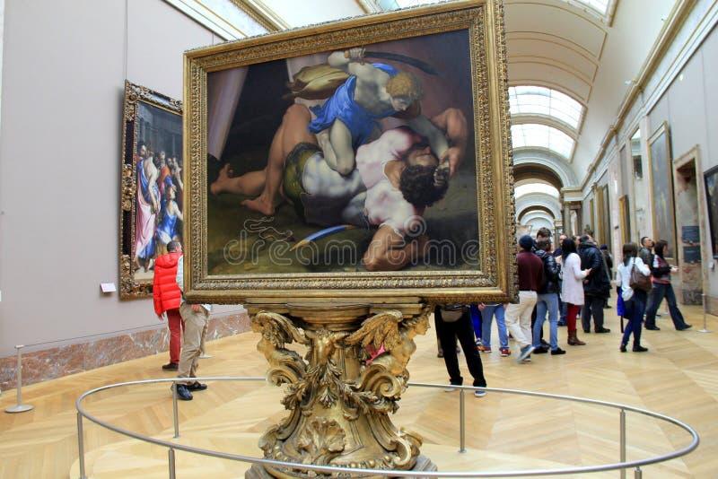Menigte van mensen die door de zalen van het Louvre lopen, waar de schilderijen, zoals David en Kolos op tentoongesteld voorwerp, stock fotografie