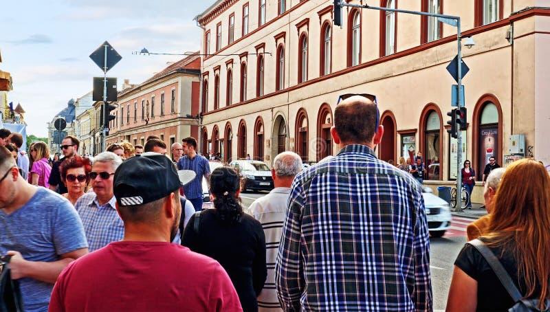Menigte van mensen die op een bezige stadsstraat lopen stock afbeelding