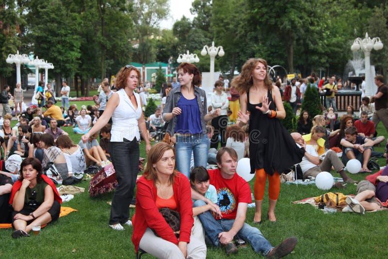 Menigte van mensen die op het gras zitten en in het Park dansen Mo royalty-vrije stock foto's