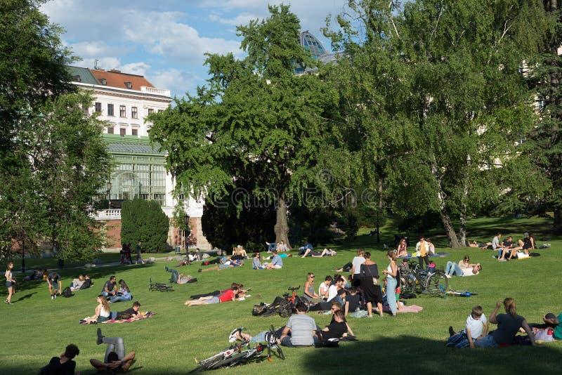 Menigte van mensen die van hete de zomerdag in een park genieten, lezing, het ontspannen royalty-vrije stock fotografie