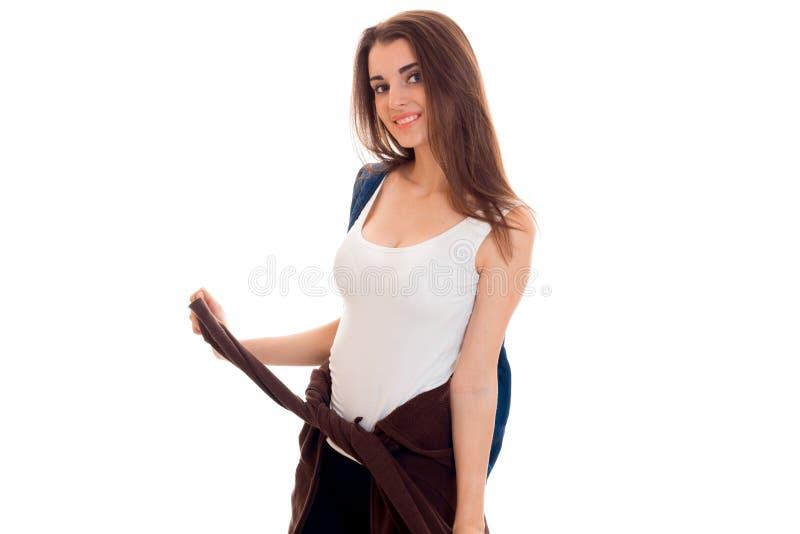 Menina à moda alegre do estudante com a trouxa em seus ombros que sorri na câmera isolada no fundo branco fotografia de stock royalty free