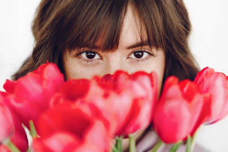 Menina à moda bonita com as tulipas cor-de-rosa no fundo branco sensor imagens de stock