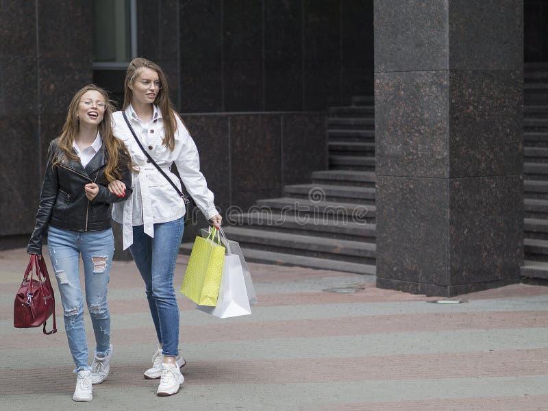 Menina à moda bonita com sacos que anda abaixo da rua fotos de stock royalty free