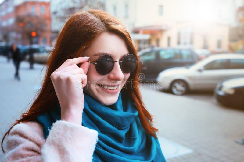 A menina à moda bonita de cabelo vermelha está andando na rua da cidade em um revestimento e em um lenço azul imagens de stock