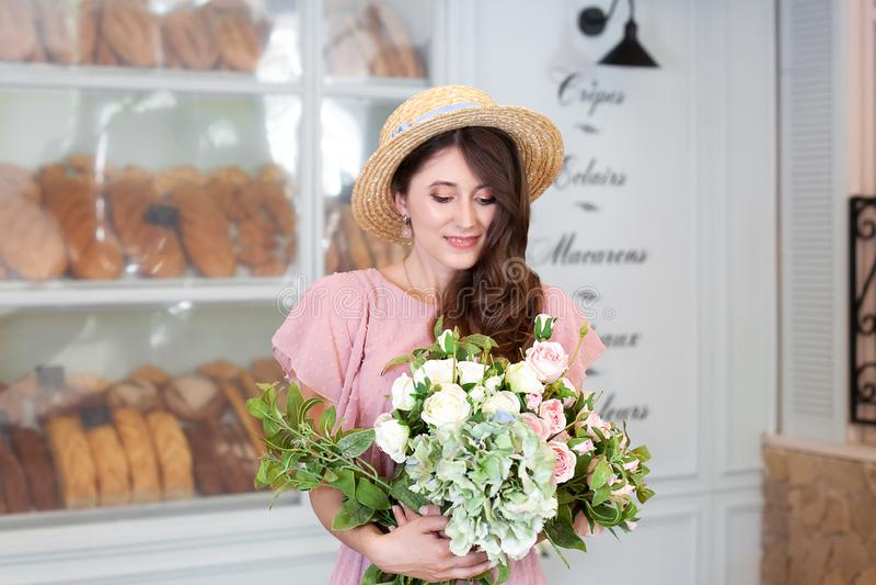 Menina à moda bonita em um chapéu do vestido e de palha do vintage no interior de uma padaria francesa Menina alegre com cabelo m foto de stock
