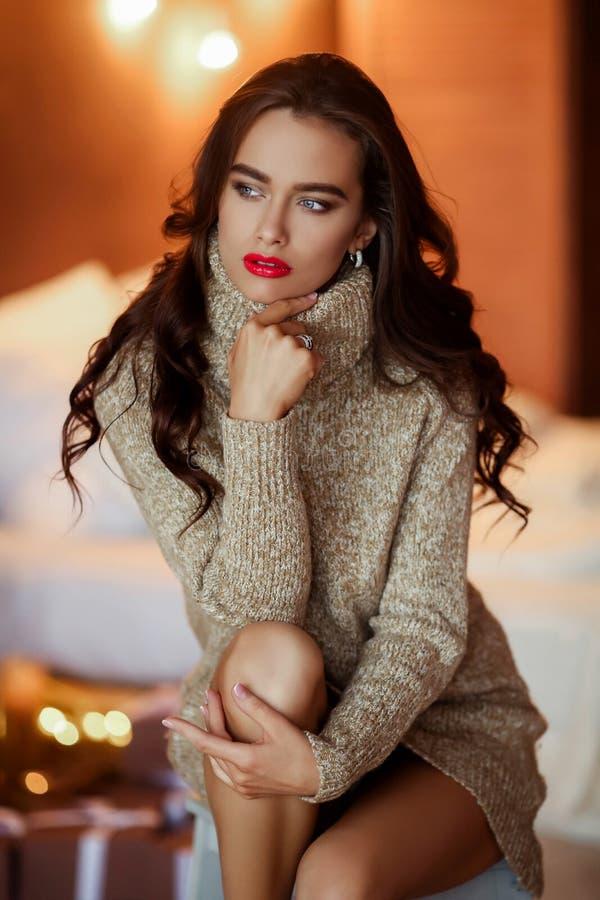 Menina à moda bonita no vestido com o penteado e a composição que sentam-se no sofá Retrato do encanto da forma imagens de stock