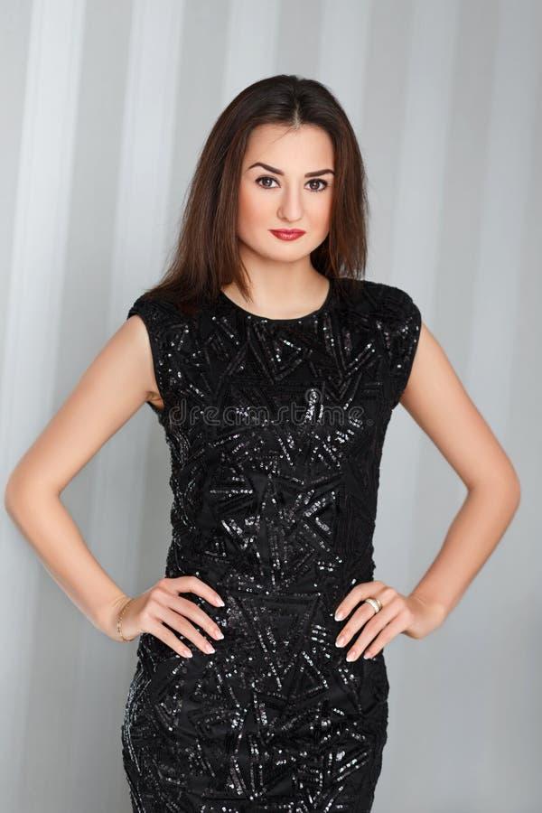 Menina à moda bonita nova com os bordos vermelhos que levantam em vestido elegante surpreendente do preto da noite imagem de stock