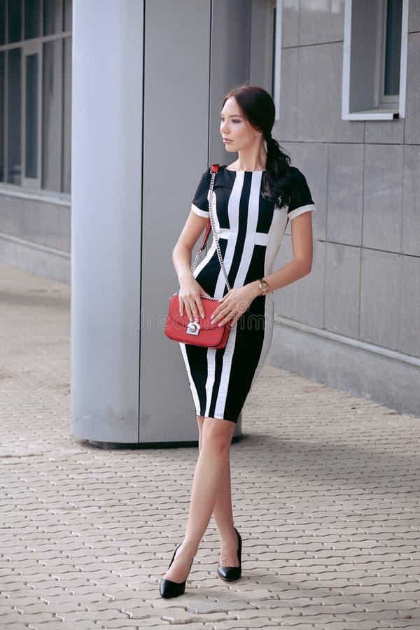 Menina à moda bonita nova em um vestido preto do verão que anda e que levanta fora imagens de stock royalty free