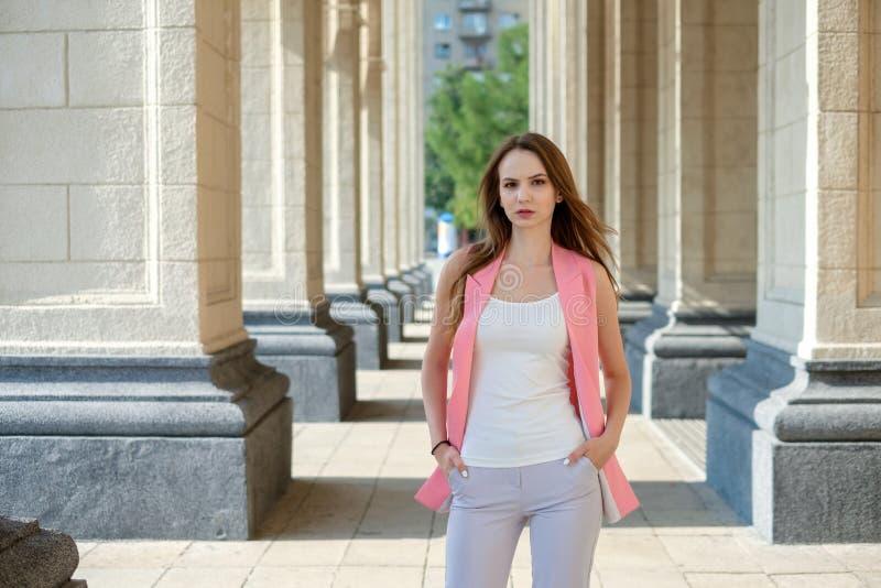 Menina à moda bonita nova que levanta em ruas da cidade do verão em um dia ensolarado foto de stock
