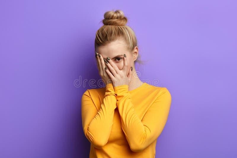 Menina ? moda bonita que esconde-se atr?s das palmas fotos de stock royalty free