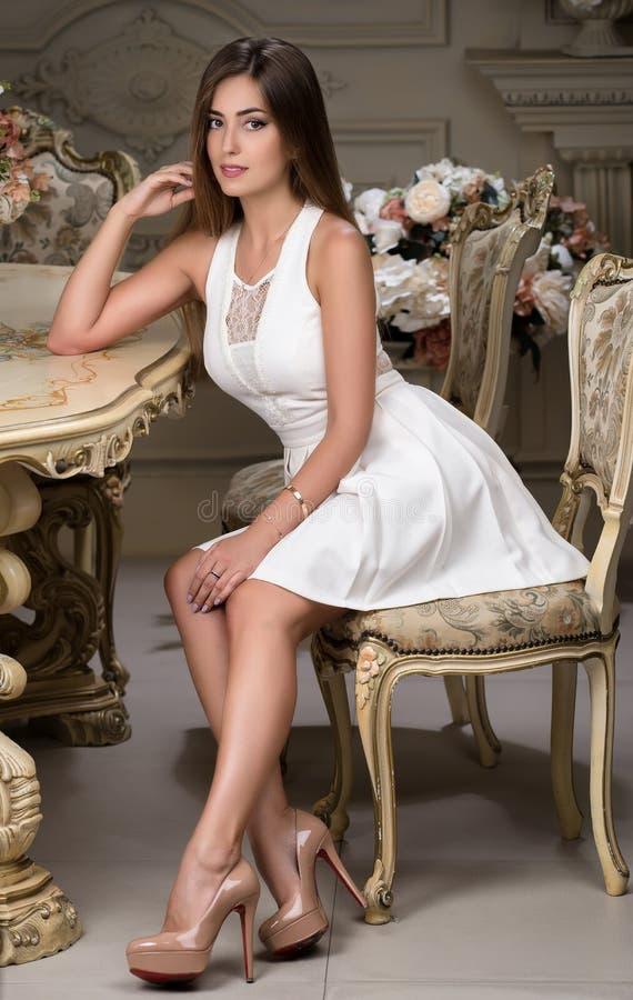 Menina à moda bonita que levanta em um estúdio interior Uma mulher está sentando-se perto de uma tabela do vintage imagem de stock