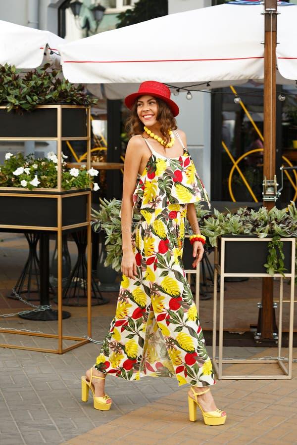 A menina à moda brilhante vestida em um vestido colorido, em um chapéu vermelho e em uns saltos altos amarelos está andando na ru fotos de stock