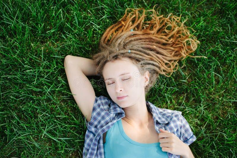 Menina à moda com os dreadlocks que encontram-se na grama verde fotos de stock royalty free