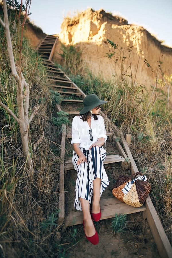 Menina ? moda do boho no chap?u que senta-se em escadas de madeira na luz ensolarada no penhasco arenoso perto do mar Mulher eleg fotos de stock