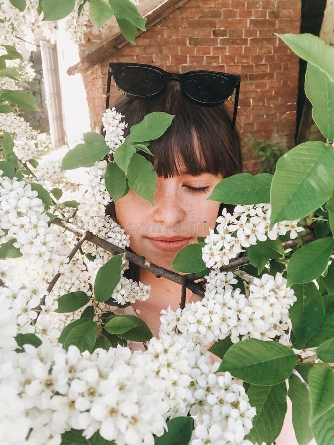 Menina à moda do boho que toma o selfie com as flores brancas em ramos verdes da árvore da pássaro-cereja Retrato da menina com a imagem de stock
