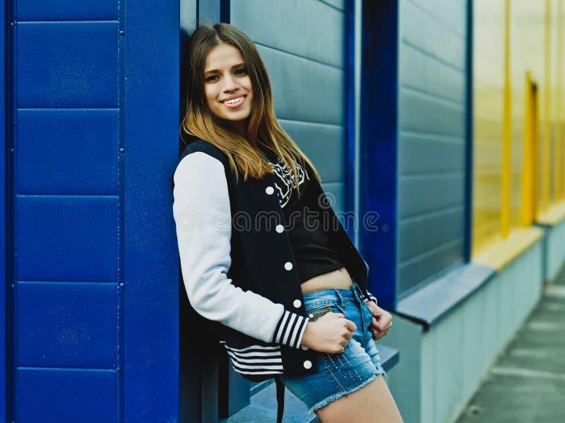 Menina à moda do moderno contra a parede colorida na cidade fotografia de stock