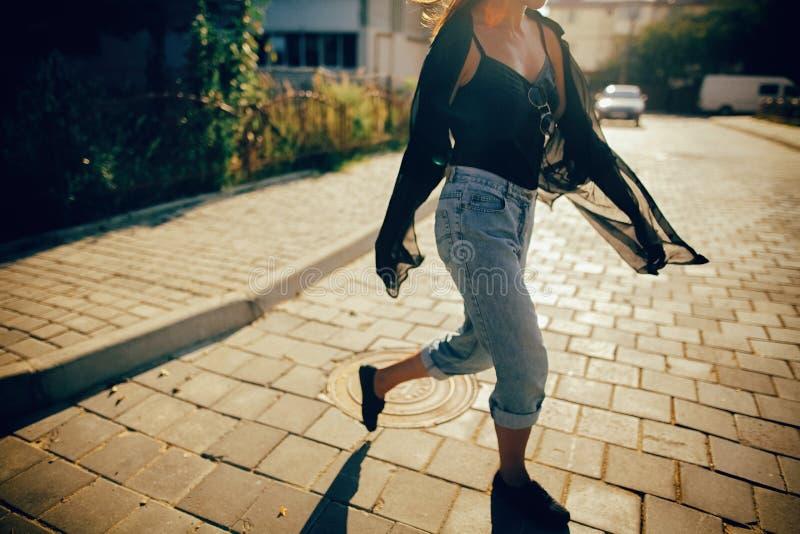 Menina à moda do moderno que anda na luz ensolarada na rua, momento atmosférico Mulher fresca elegante em cal?as de brim da sarja foto de stock