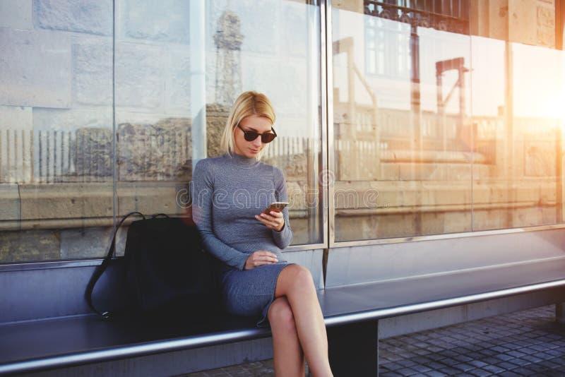 Menina à moda do moderno que conversa na rede através do telefone esperto com seus amigos ao se sentar na parada do ônibus no dia imagens de stock royalty free