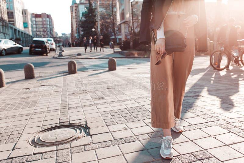 Menina à moda e elegante que anda em torno da cidade em um casaco de cabedal imagens de stock