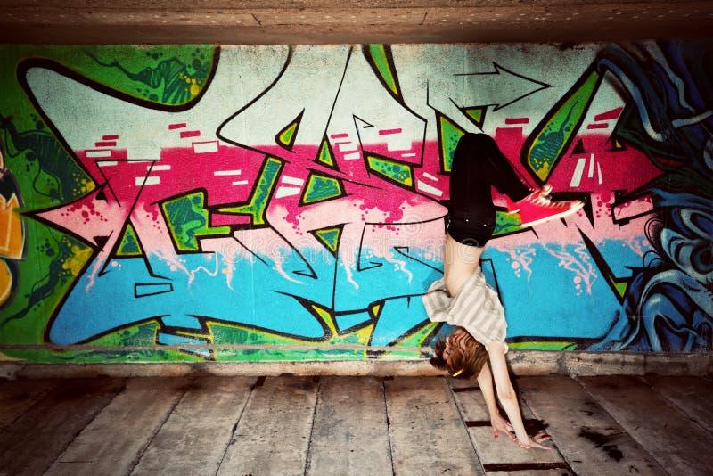 Menina à moda em uma pose da dança contra a parede dos grafittis fotografia de stock