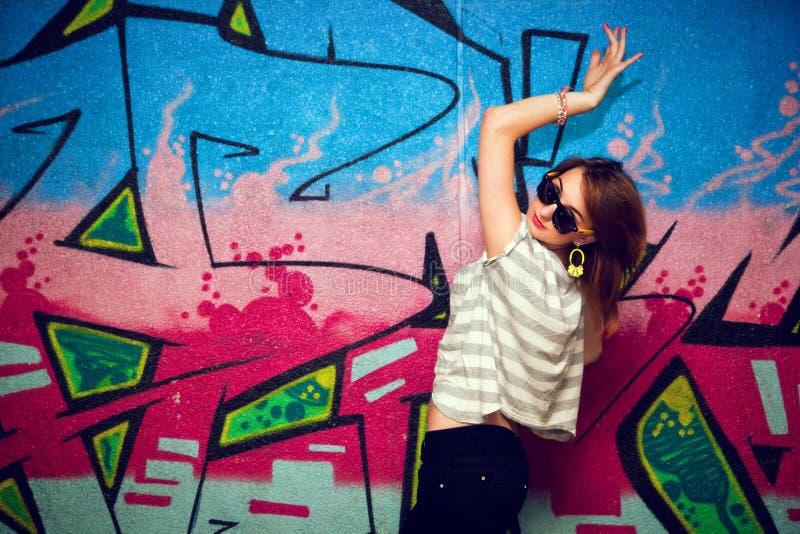 Menina à moda em uma pose da dança contra a parede dos grafittis foto de stock