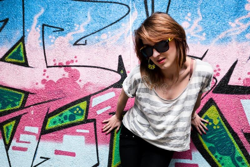 Menina à moda em uma pose da dança contra a parede dos grafittis foto de stock royalty free